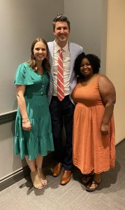 Two residents stand with school administrator Josh Fleming for a photo
