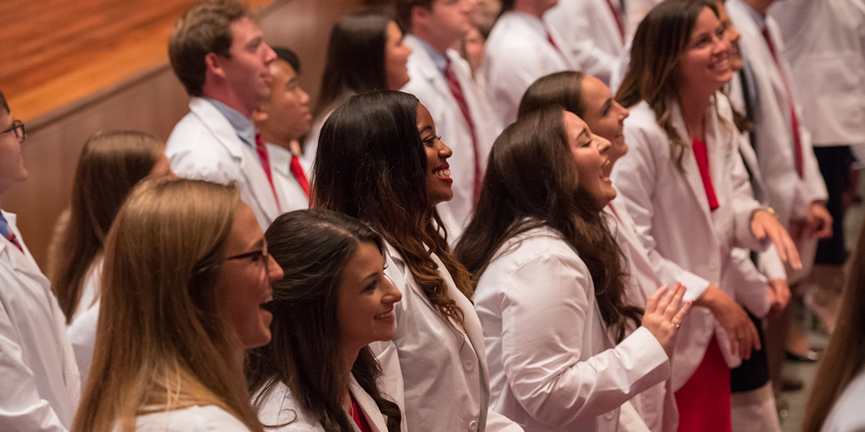 Students smiling at White Coat Ceremony