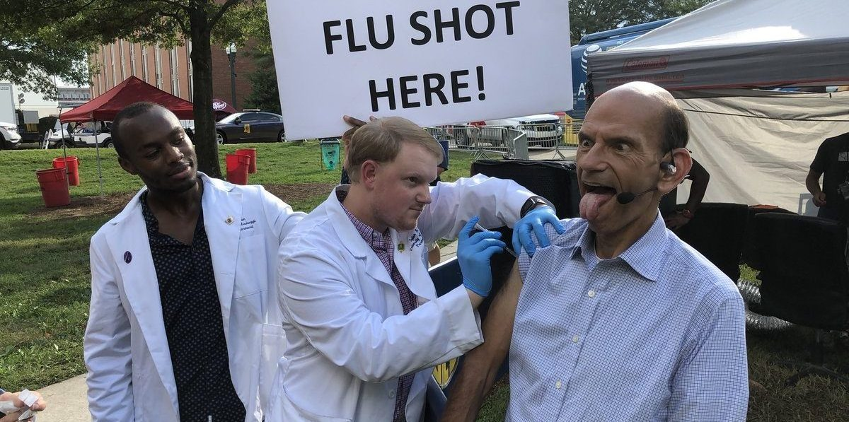 TV host Paul Finebaum gets his flu shot from two male students
