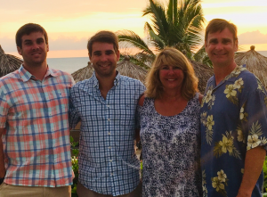 Two brothers stand next to their mom and dad in beach setting.