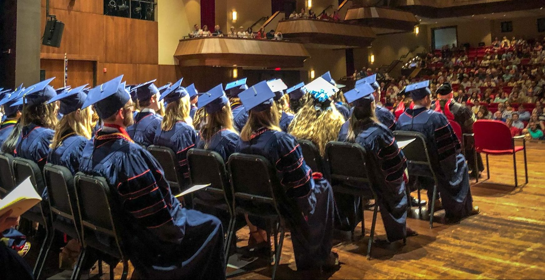 Graduates in cap and gown sit on the stage and look out into crowd