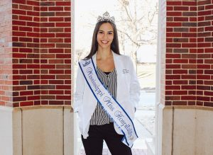 Kasey Pearson in her pharmacy white coat with pageant crown and sash