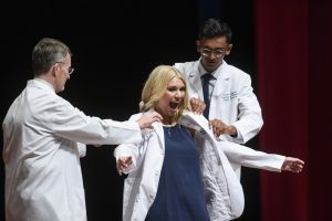 A female student shows excitement as she dons her white coat.