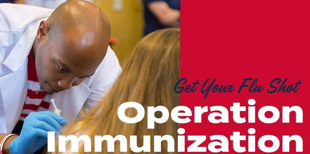 "Male student gives a flu shot; text ""get your flu shot; operation immunization"""