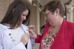 Two people looking at pins on a student's white coat